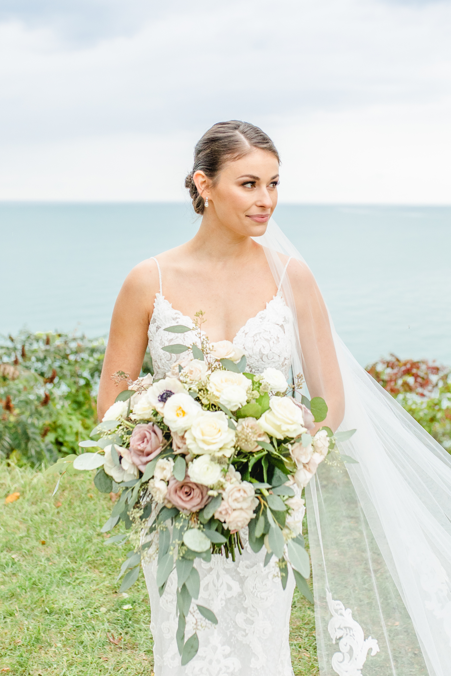 Bride looking off holding bouquet at the lakehouse wedding