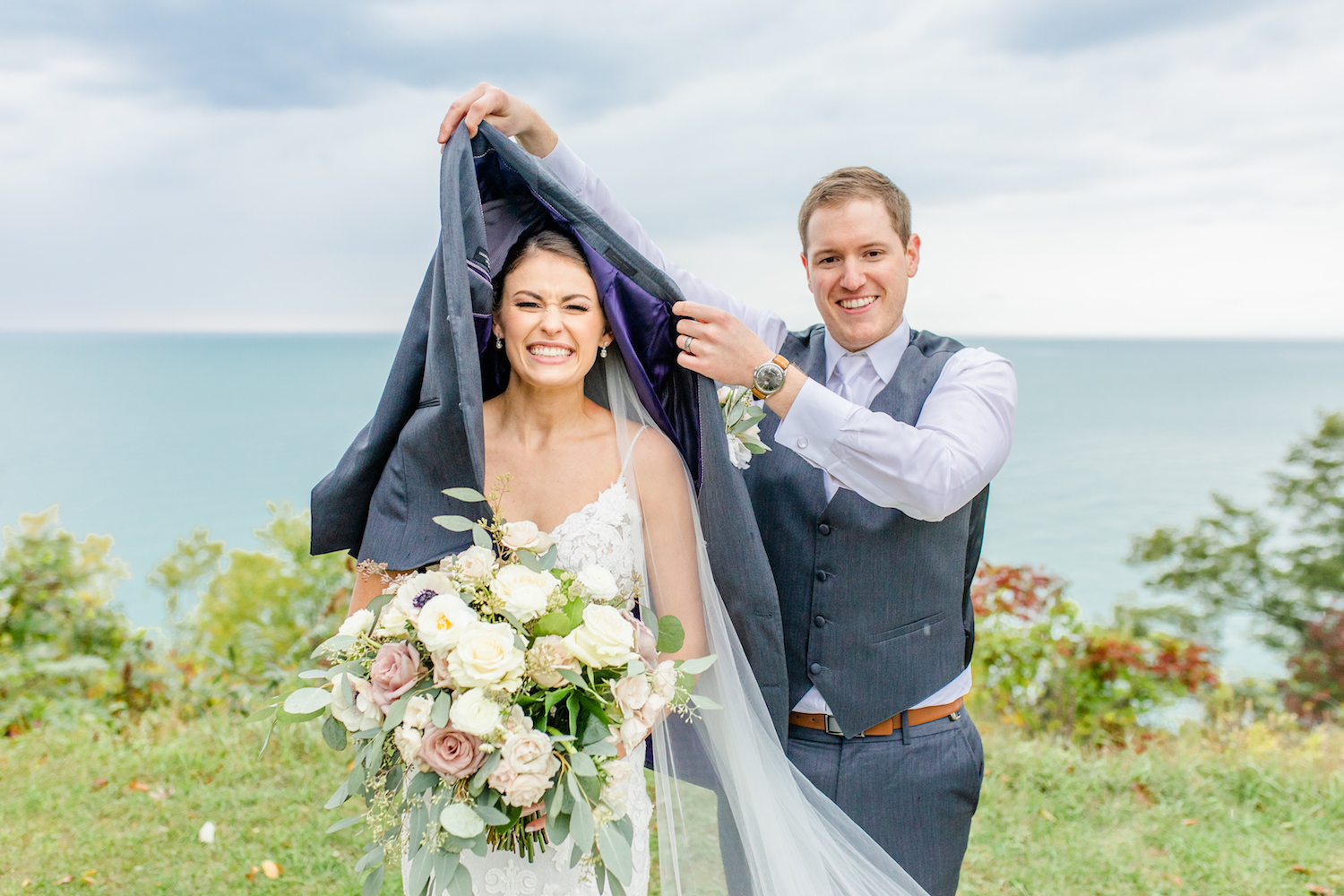 Groom covering bride at their lakehouse wedding