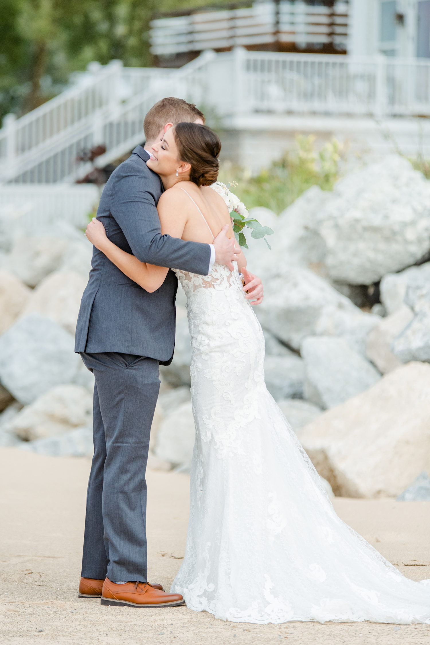 Bride and groom hugging at the lakehouse wedding