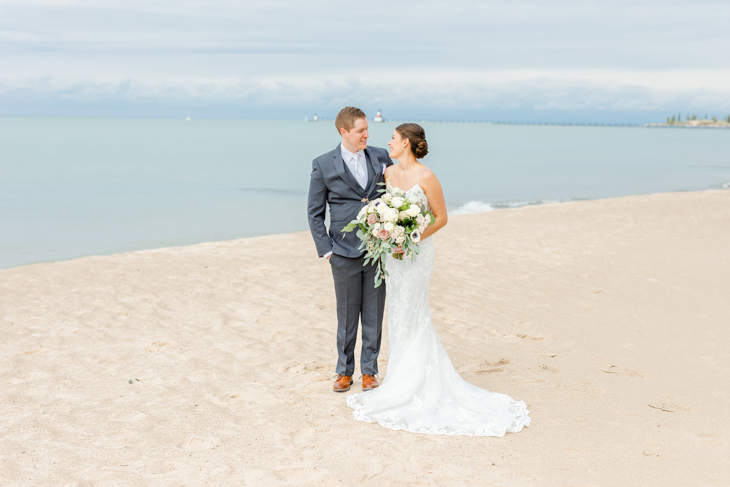 Bride and groom smiling at beach of the lakehouse wedding