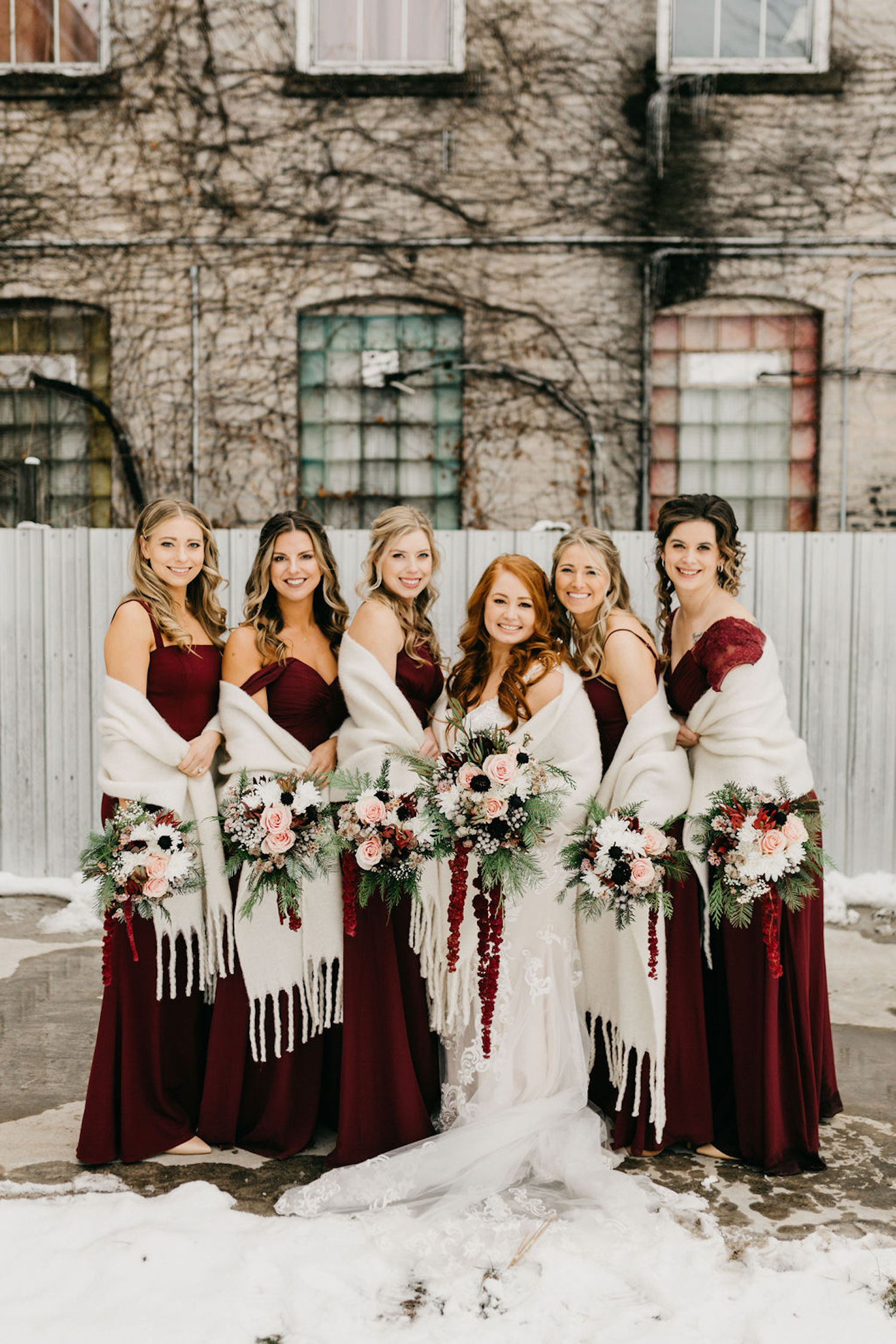 Bridal party standing in snow before Journeyman distillery wedding