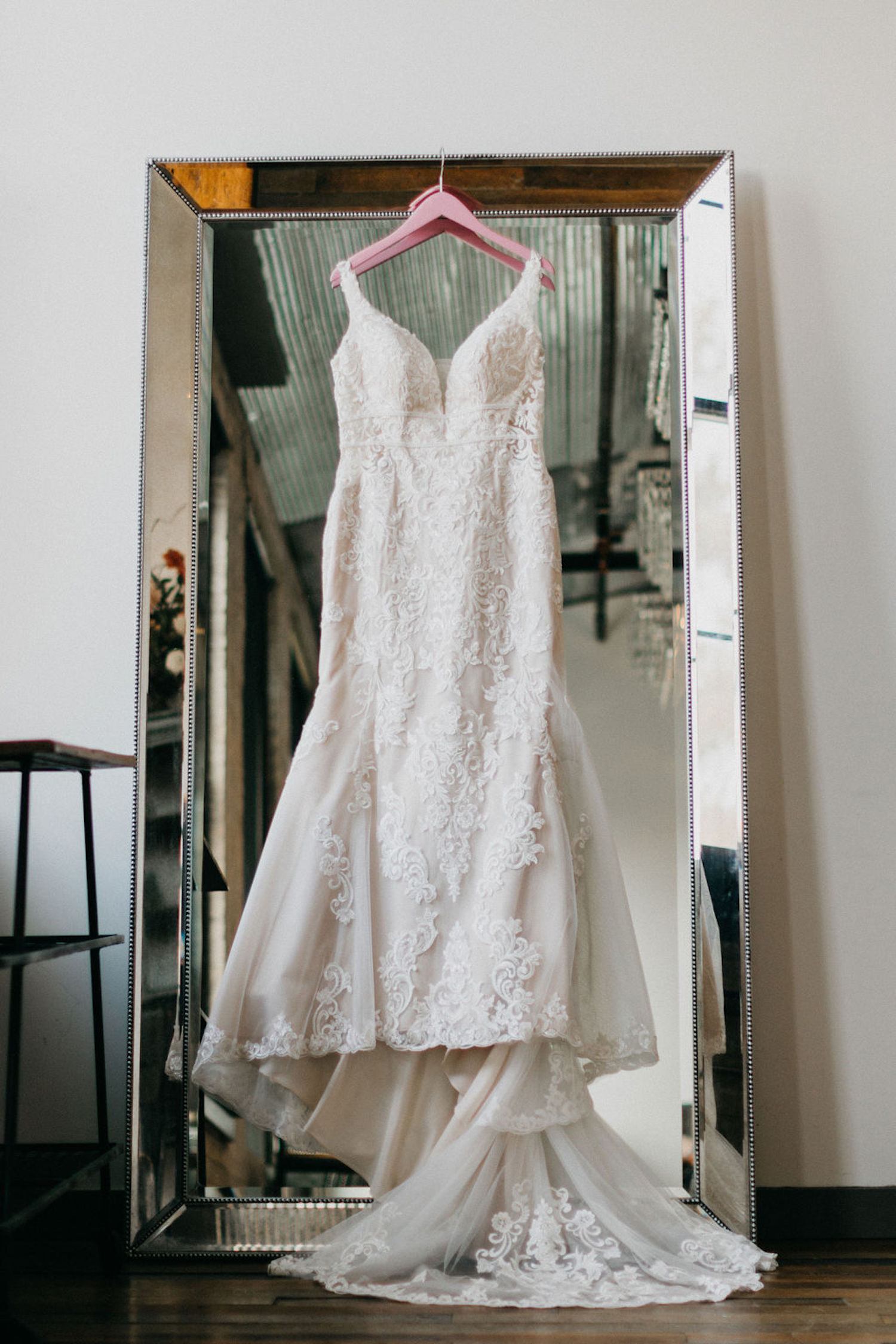 Wedding gown hanging in front of mirror