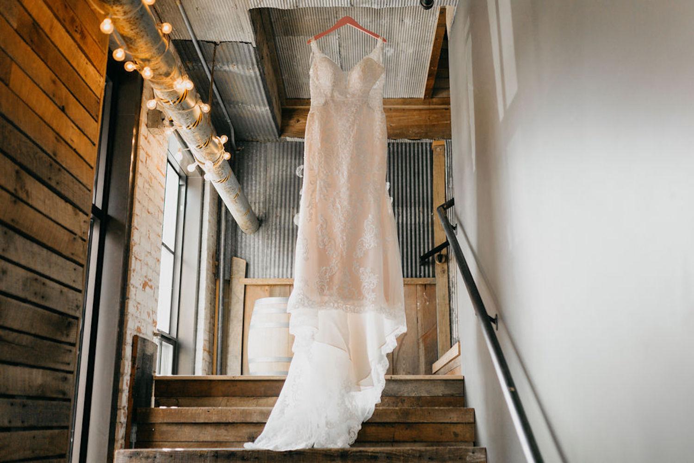Journeyman Distillery Wedding gown hanging in stairway