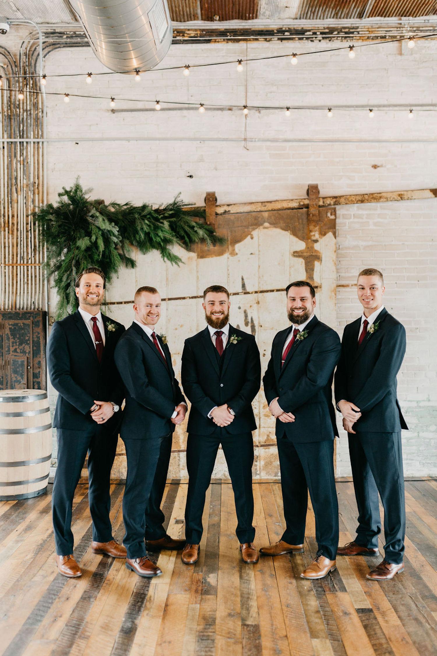 Grooms and groomsman standing before Journeyman Distillery wedding