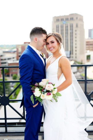 Bride and groom on rooftop smiling