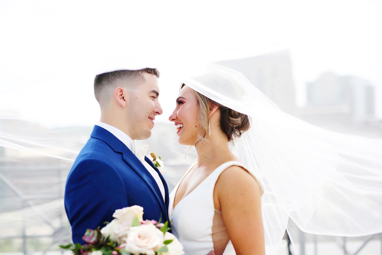 Bride and groom smiling under her veil