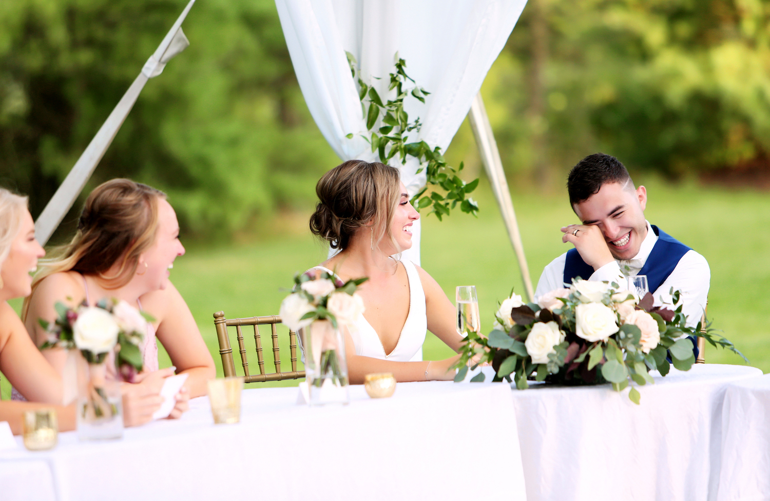 Bride and groom smiling at the head table