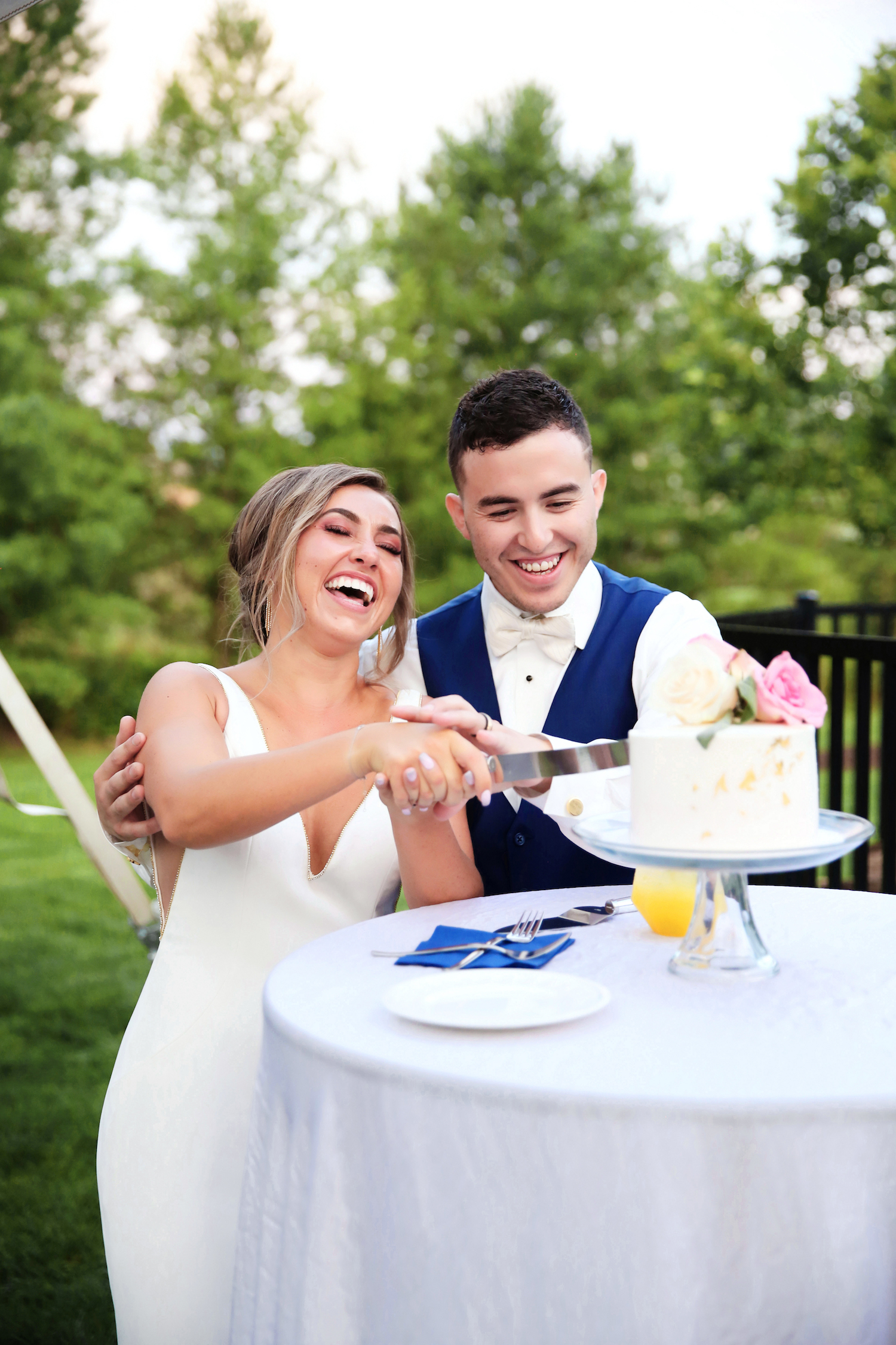 Bride and Groom smiling while cutting their cake