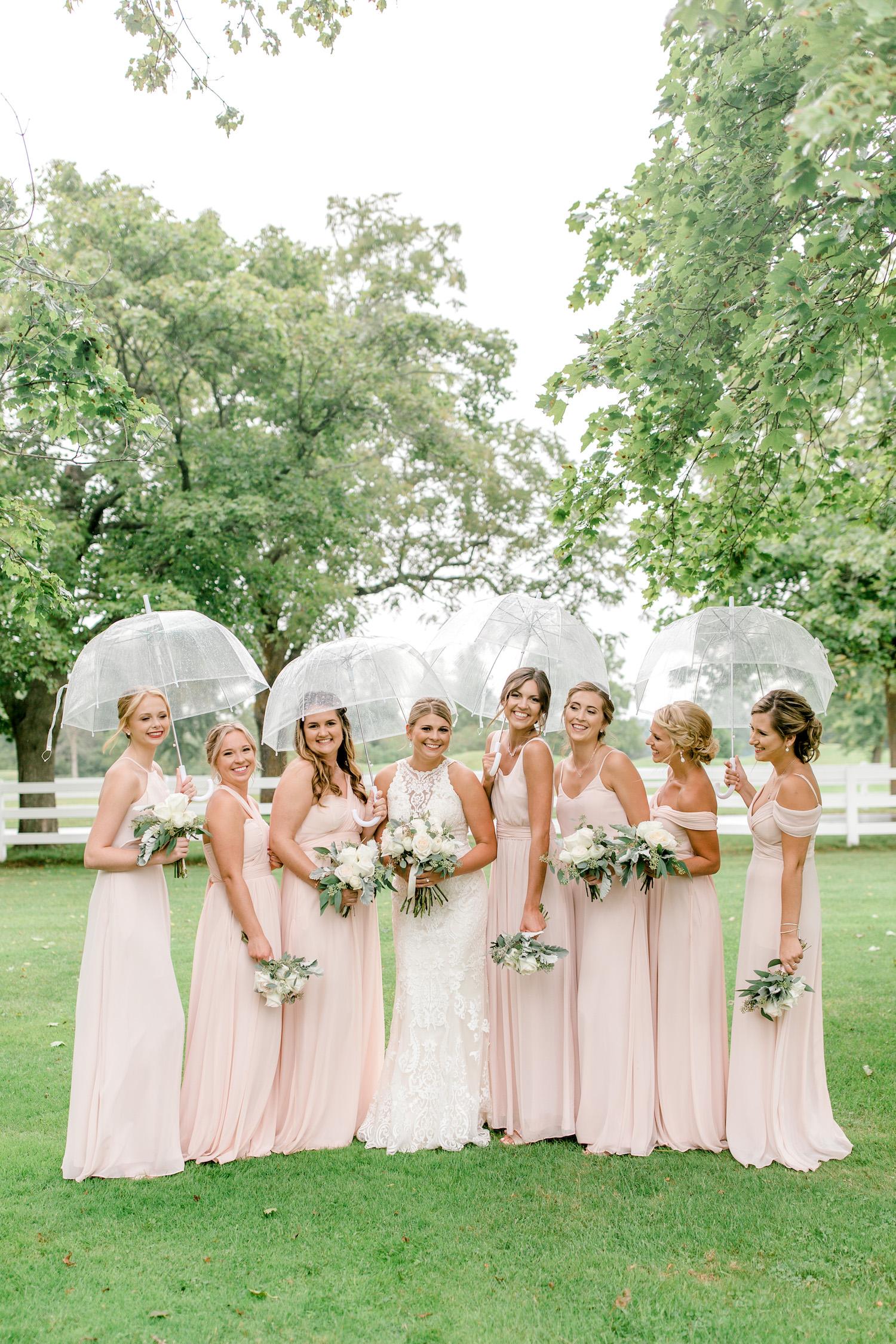 Bride and bridesmaids standing under umbrellas
