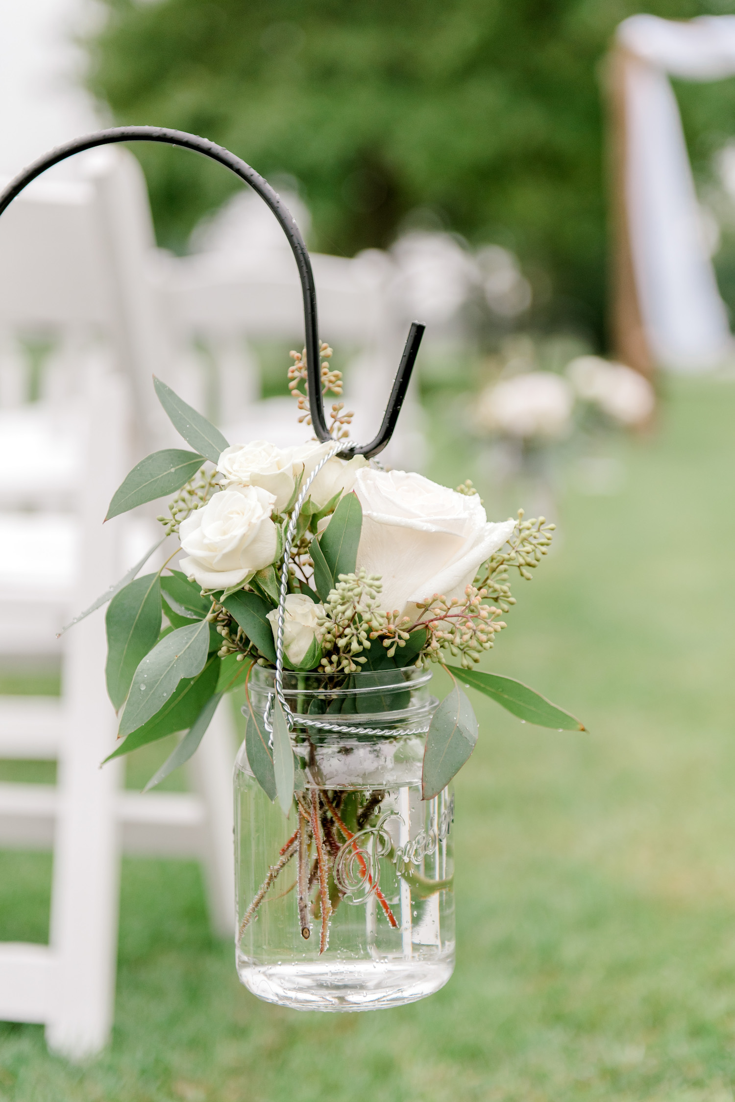 Rose arrangement in jar hanging from hooks