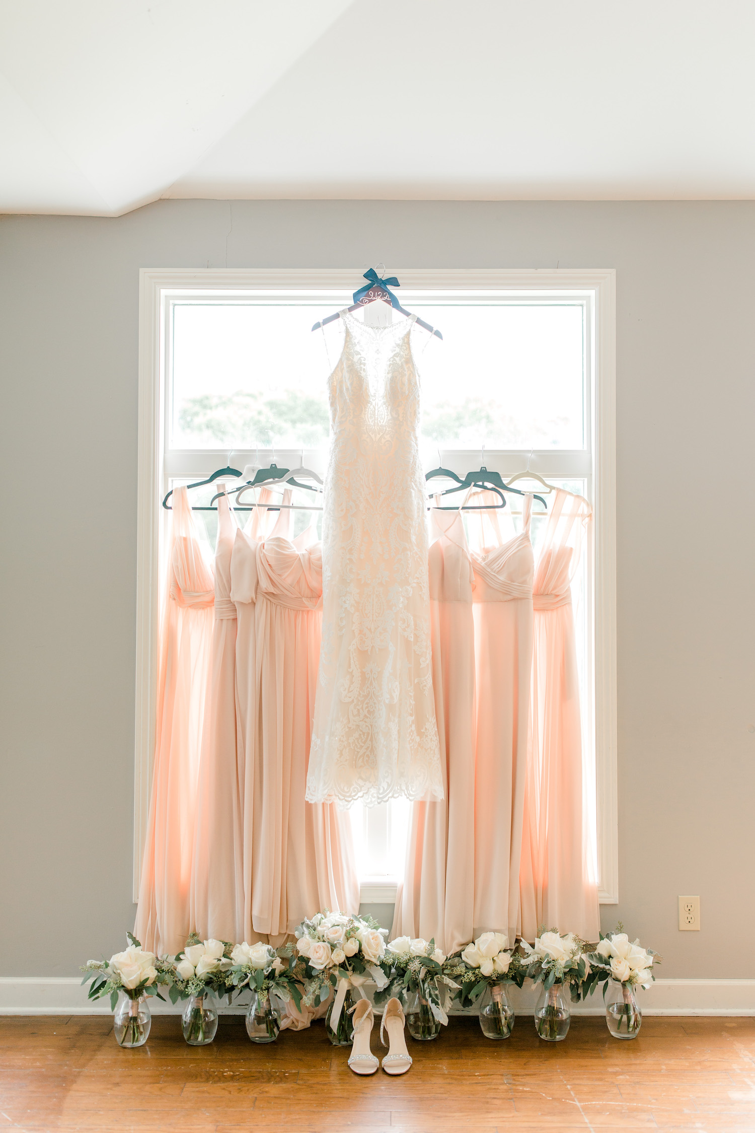 Brides dress hanging with bridesmaids dresses