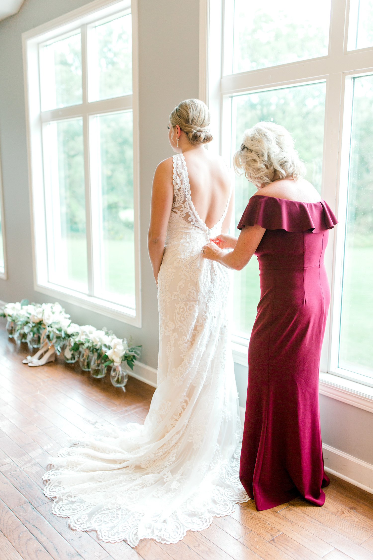 Mother of bride buttoning brides gown