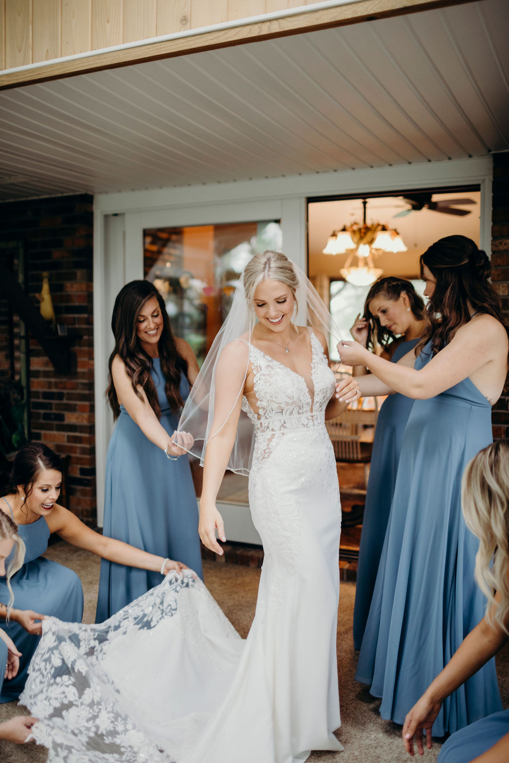 Bridesmaids smiling at brides gown