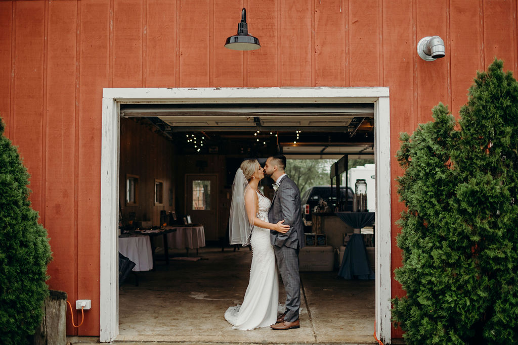 Bride and groom kissing in front of barn of Frankfort, IL Wedding