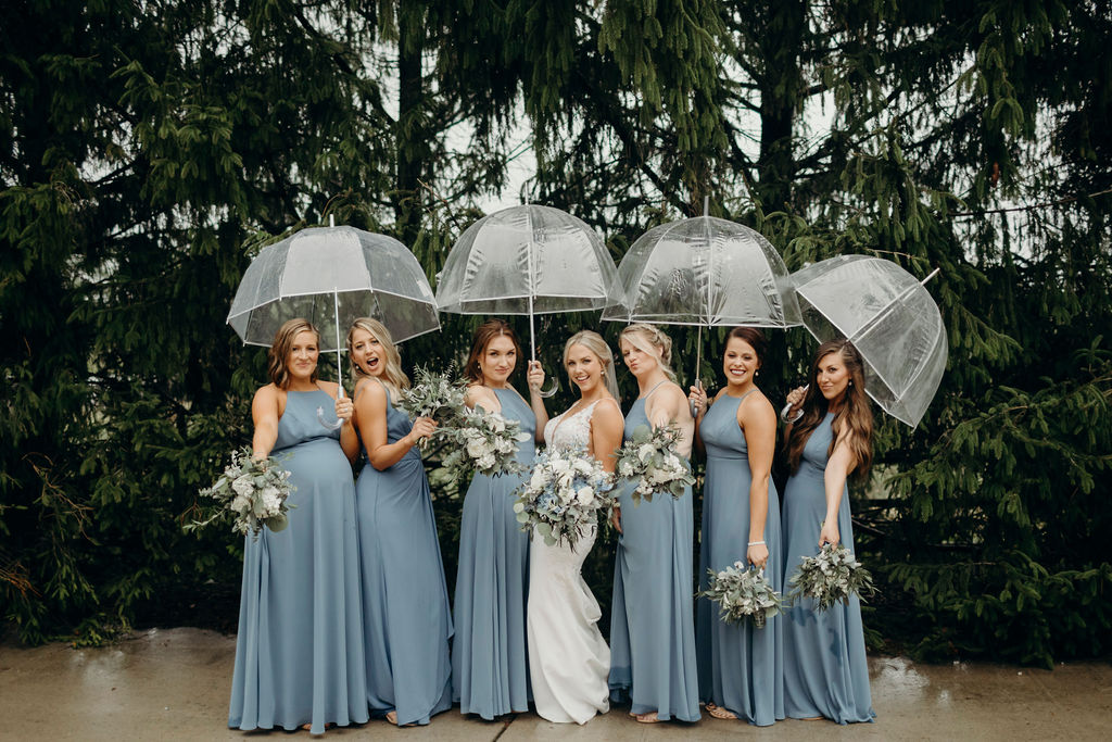 Bride and bridesmaids under umbrellas