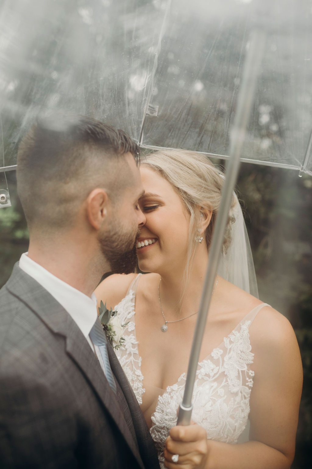 Bride and groom smiling under umbrella