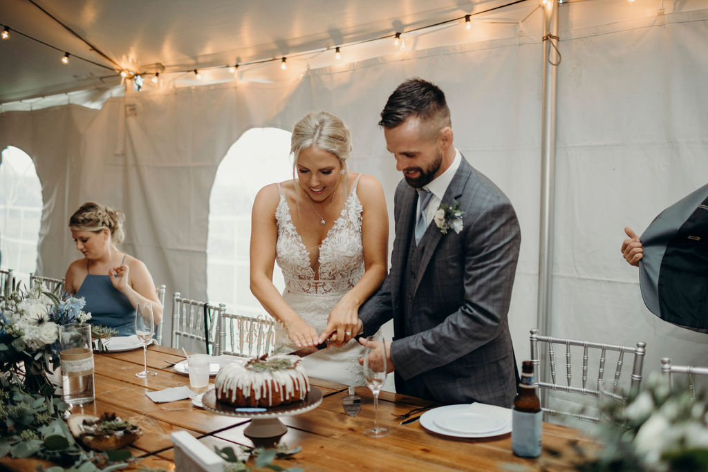 Bride and groom smiling cutting cake