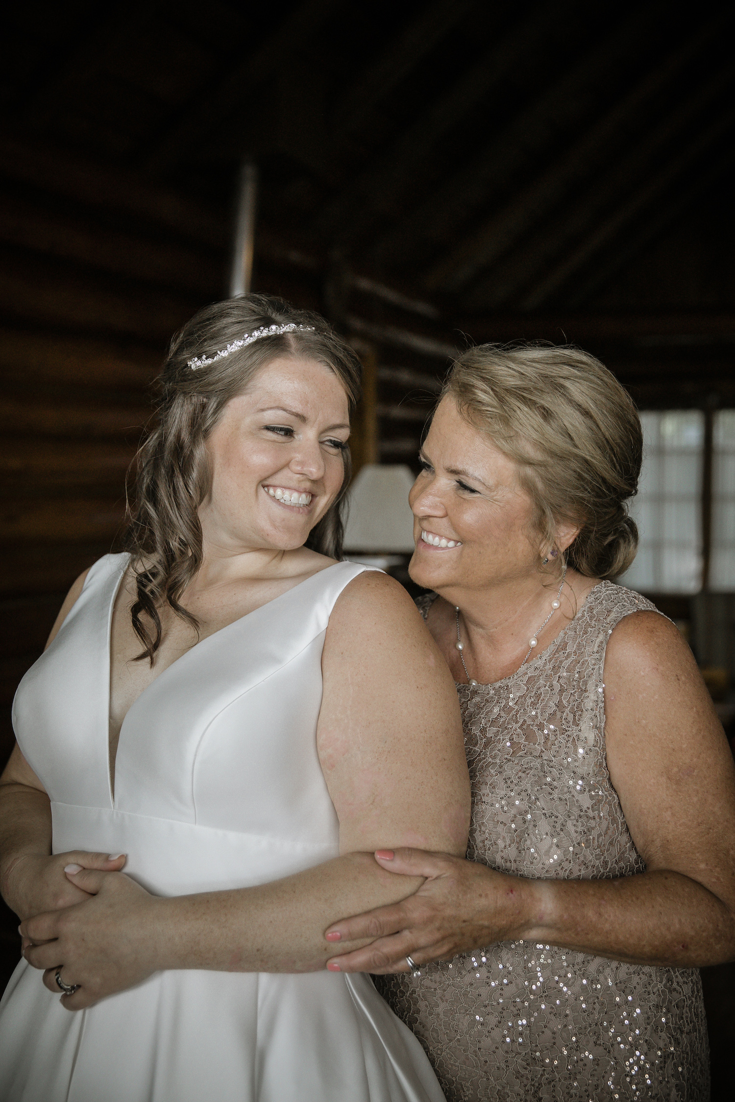 Bride and mother of bride smiling at each other