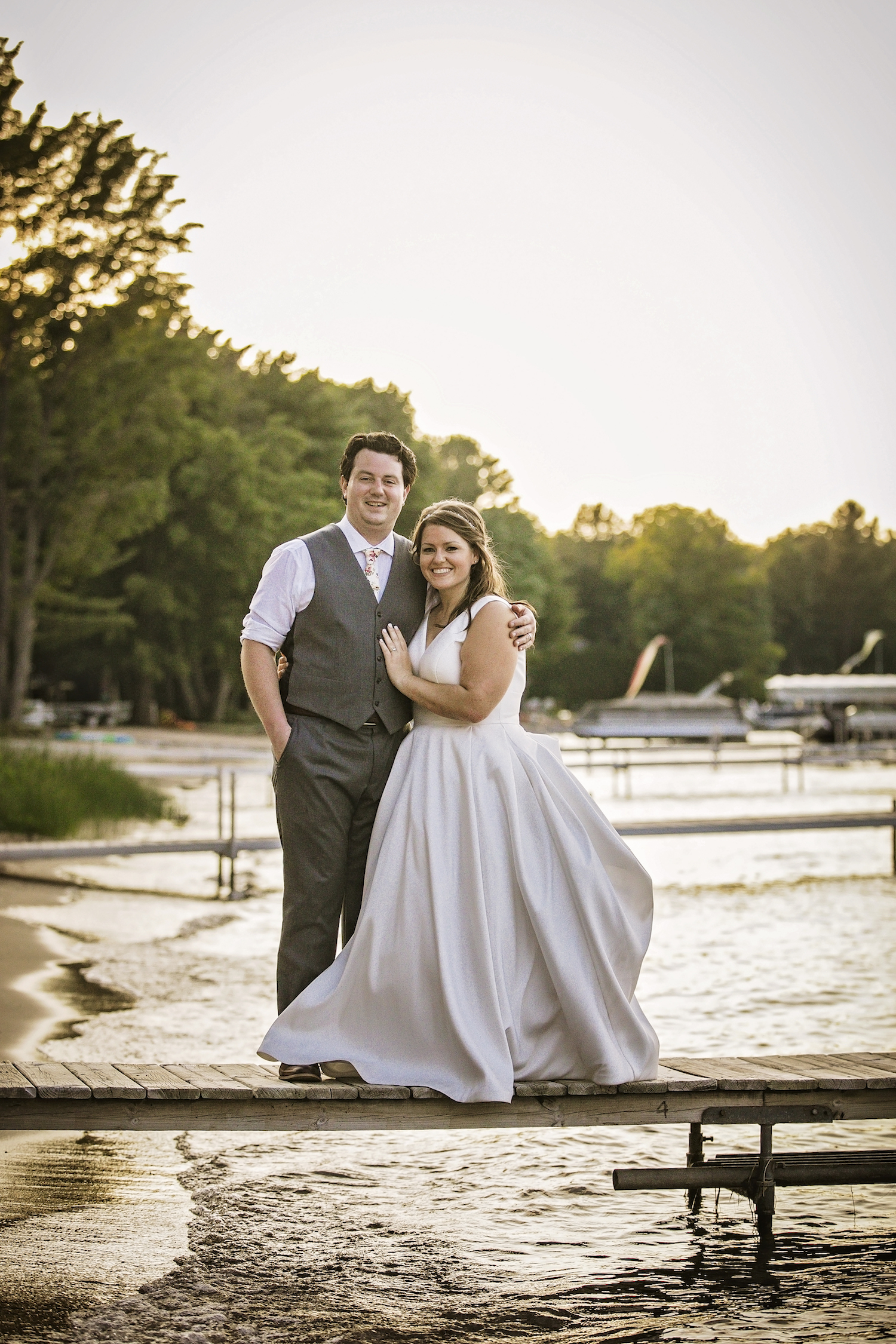 Bride and groom standing on lake dock