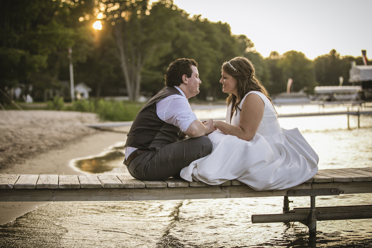 Bride and groom sitting on dock at Higgins Lake wedding
