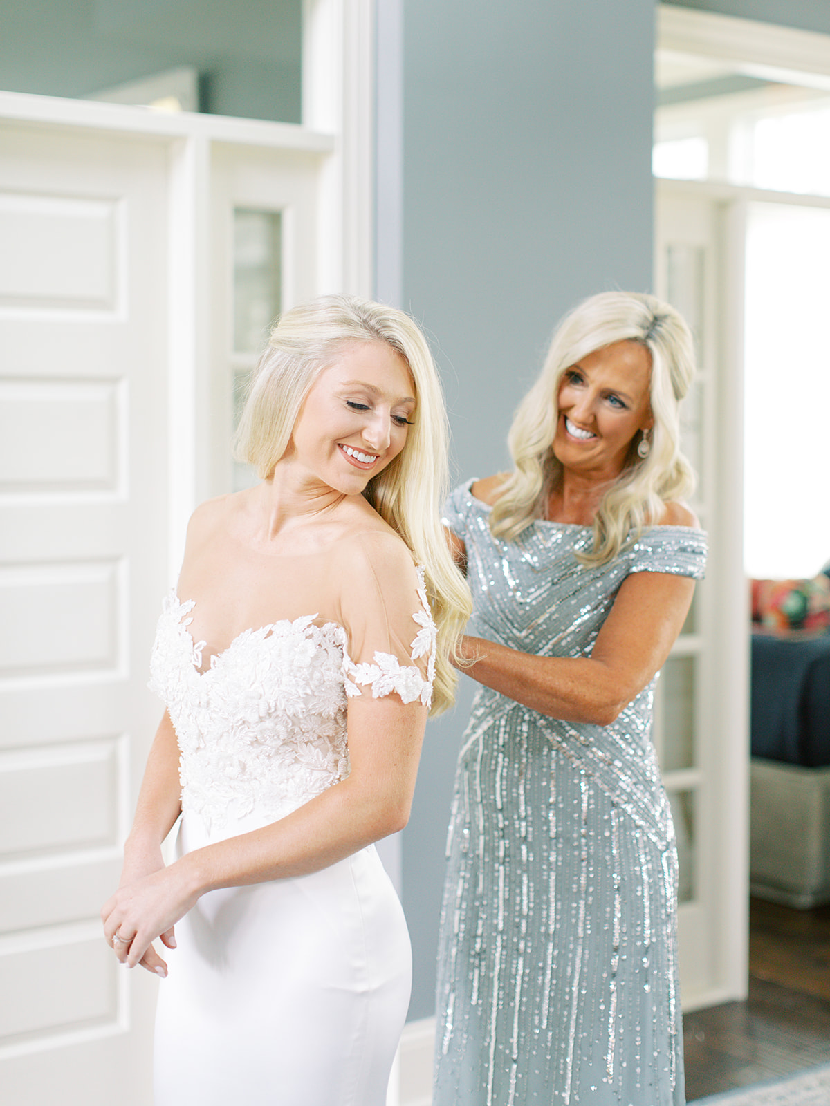 Mother of Bride buttoning bride's gown