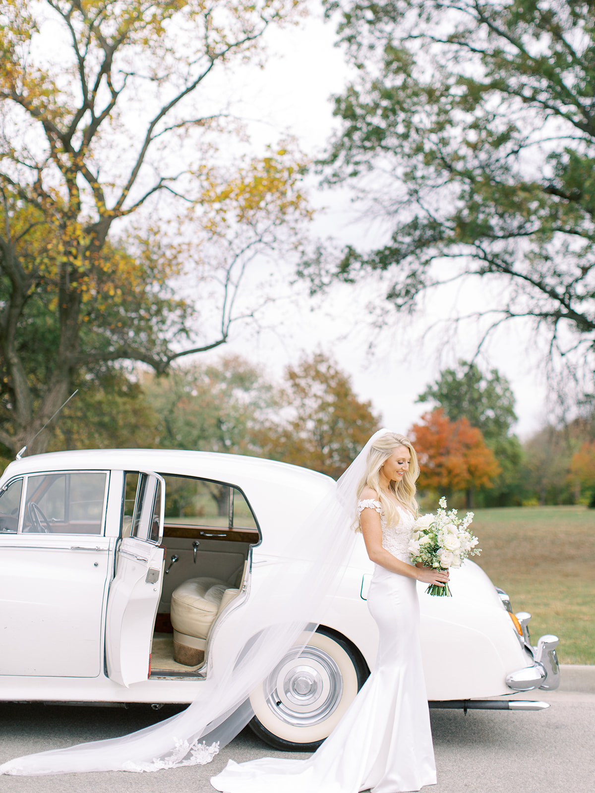 Bride smiling at bouquet in front of classic car