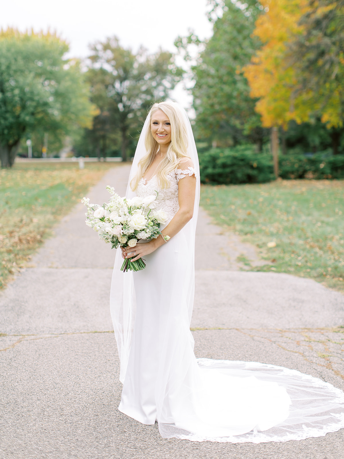 Bride standing in driveway with bouquet before Ritz Charles wedding