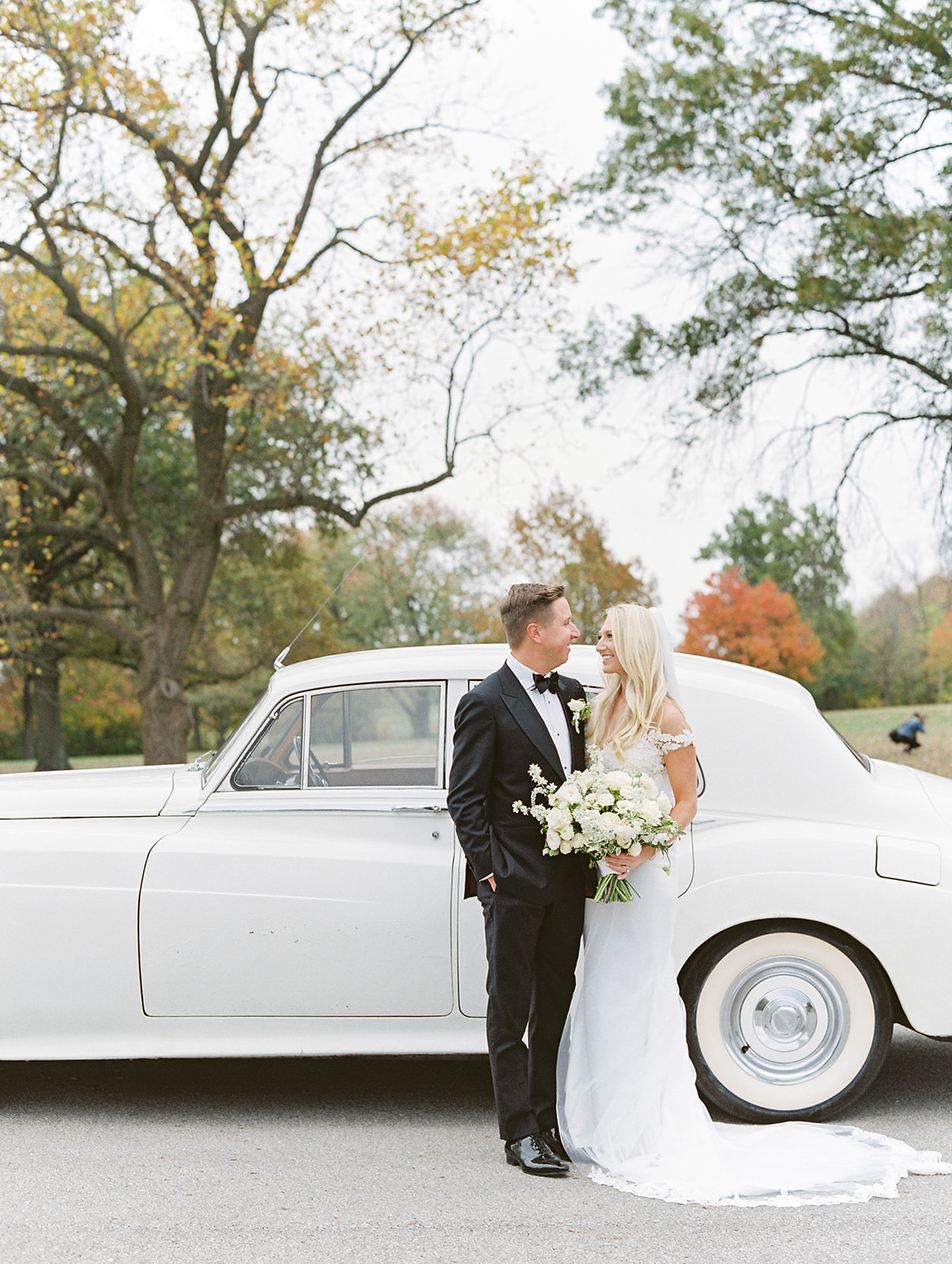 Bride and groom looking at each other in front of classic car