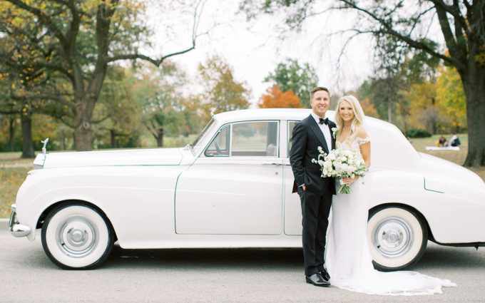 Bride and groom standing outside of classic car