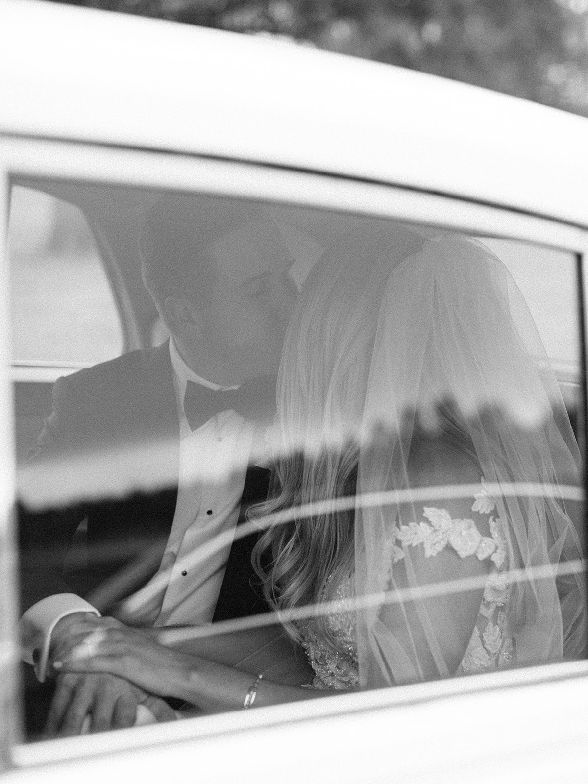 Bride and groom kissing inside of car