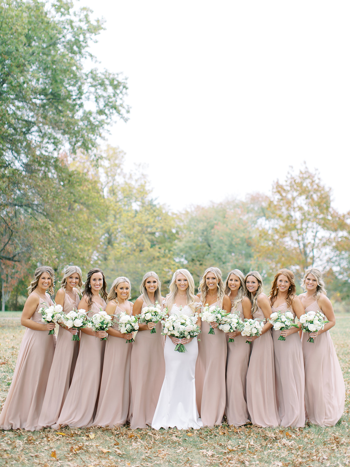 Bride standing with bridesmaids holding bouquets