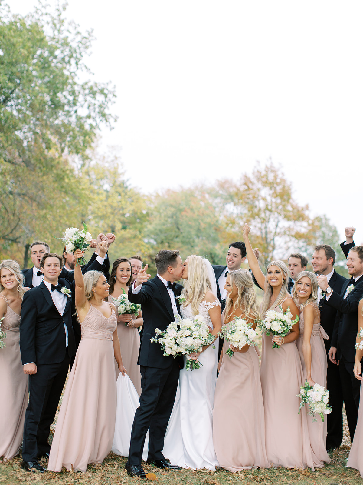 Bridal party cheering on bride and groom kissing