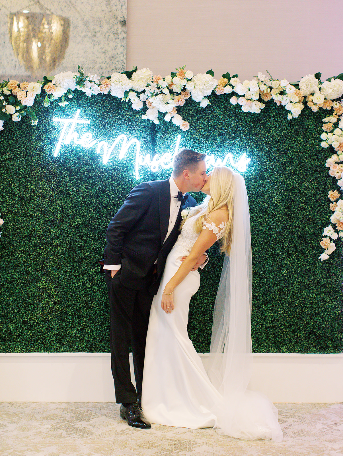 Groom kissing his bride in front of neon sign at Ritz Charles Wedding