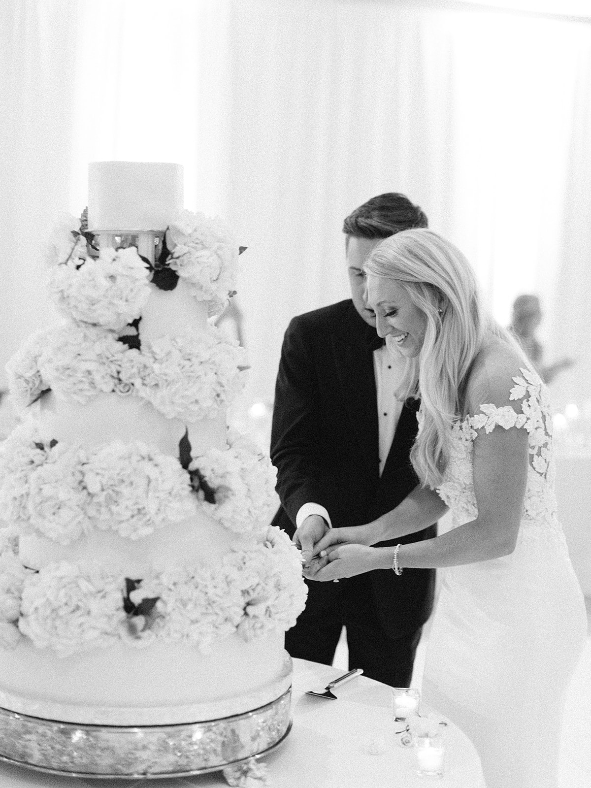 Bride and groom smiling cutting their cake