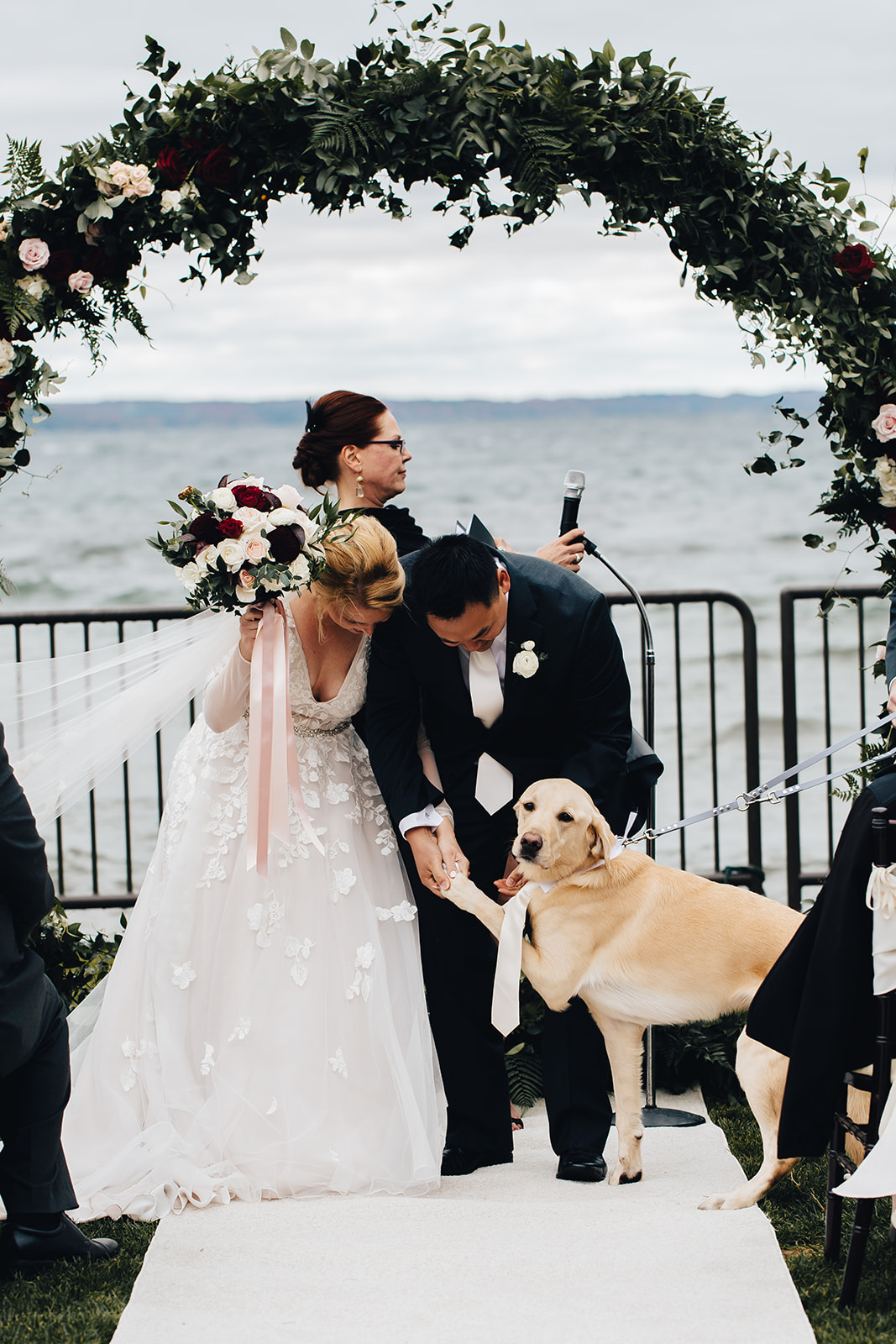Bride and groom smiling at their dog at alter