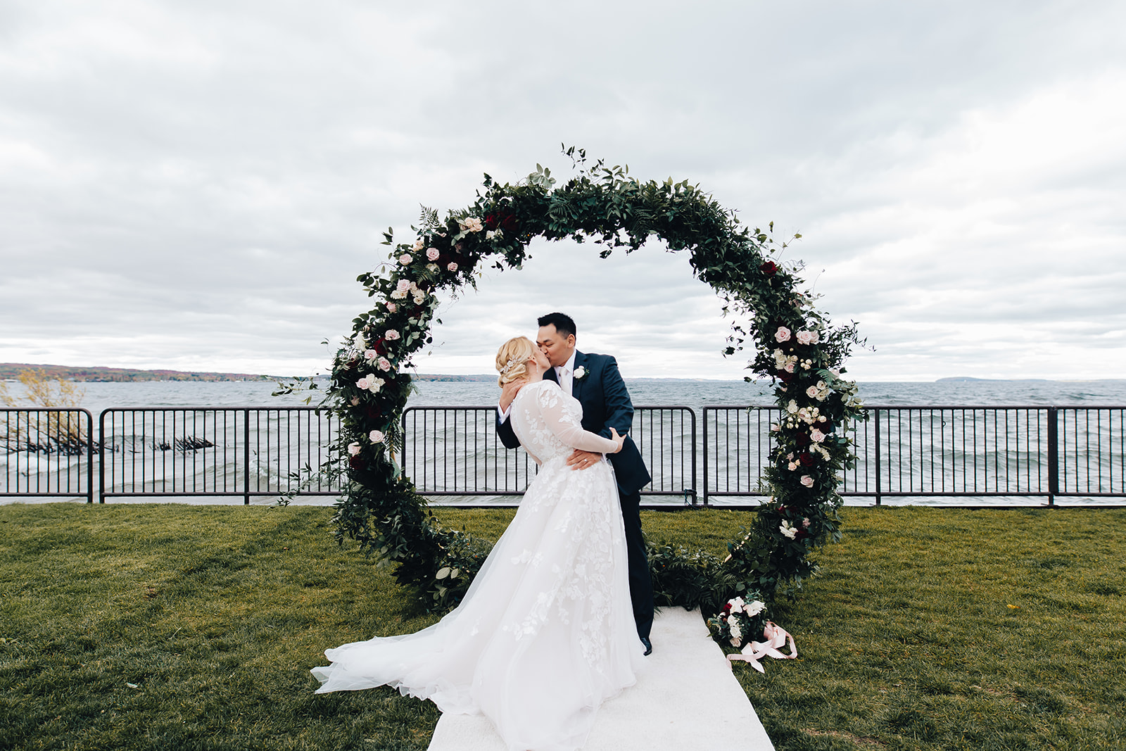 Groom kissing his bride at the hoop arch
