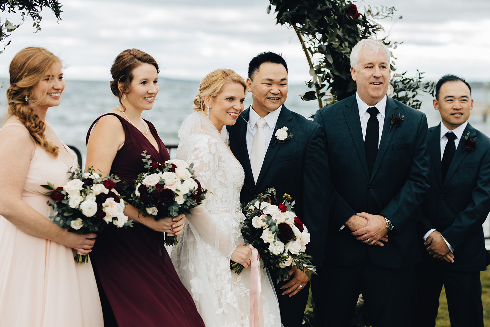 Bridal party smiling together by water