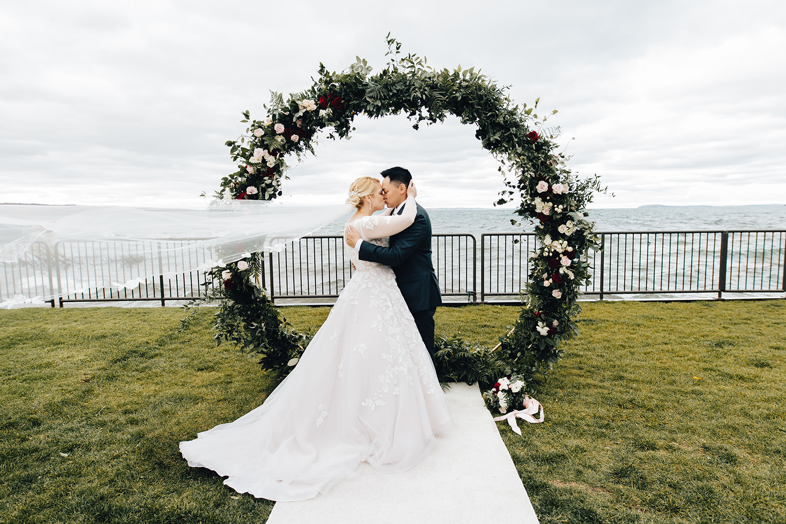 Bride and groom kissing by water of West Bay Beach wedding