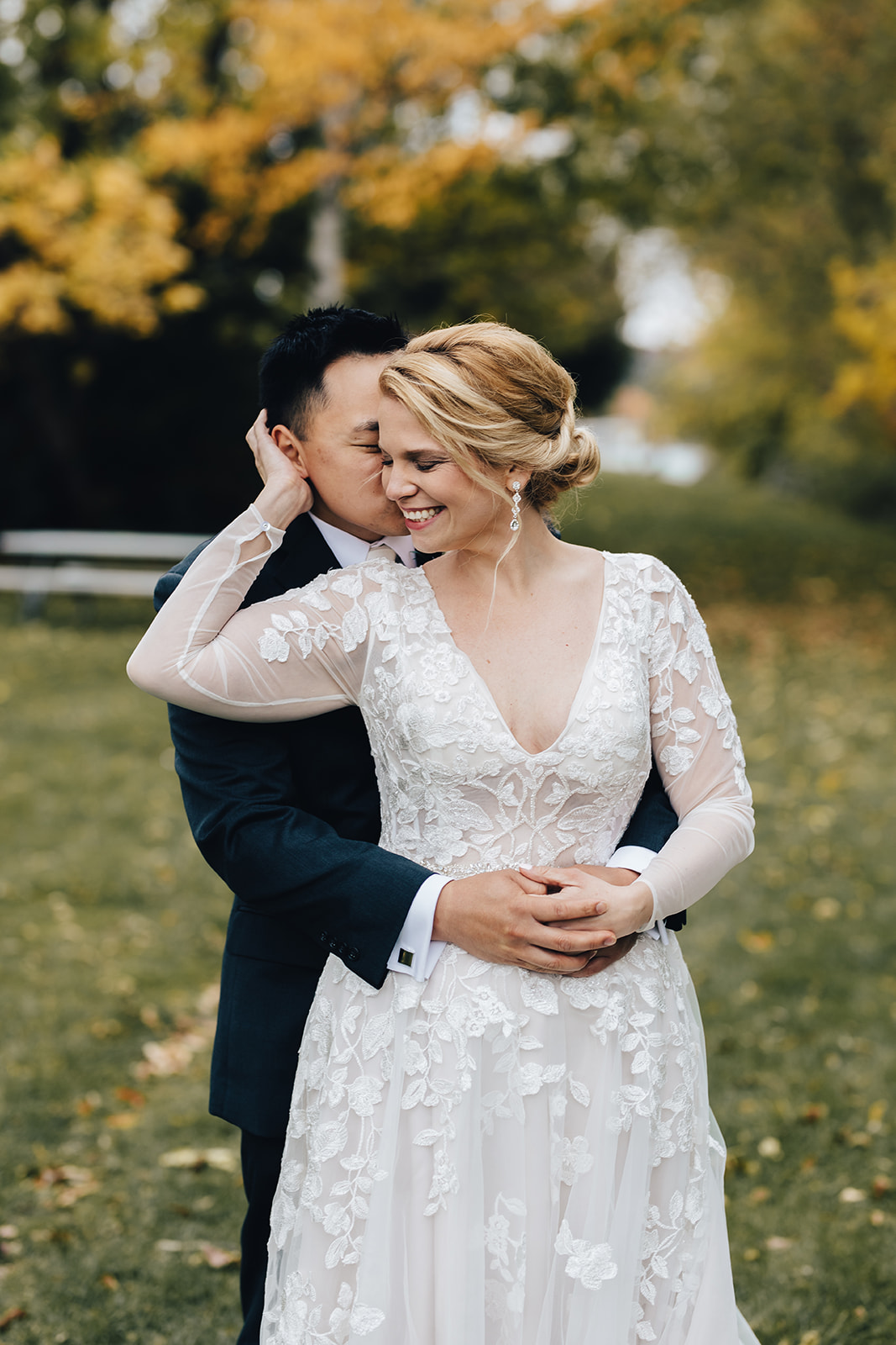 Groom holding his bride from behind while she smiles