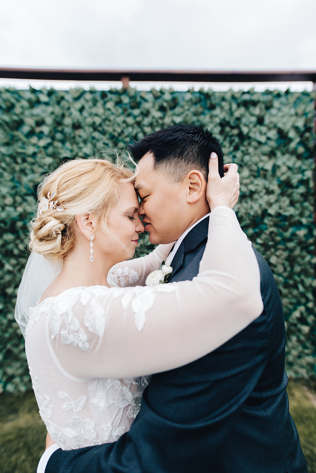 Bride and groom leaning foreheads together