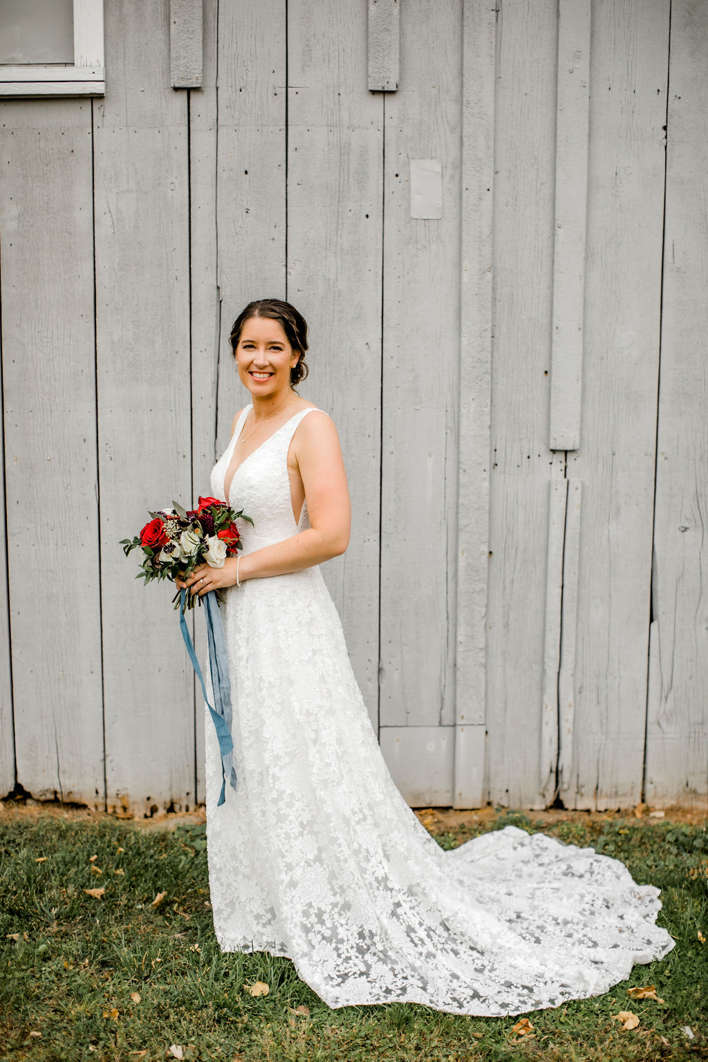 Bride smiling holding her bouquet before Jackson, MI wedding