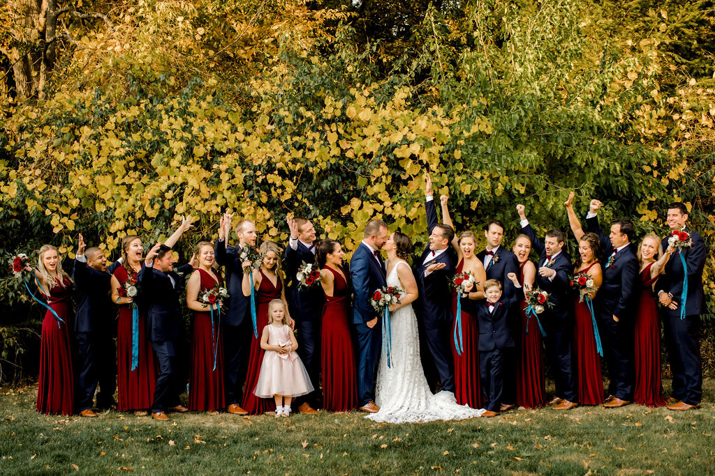 Bridal party cheering at bride and groom kissing