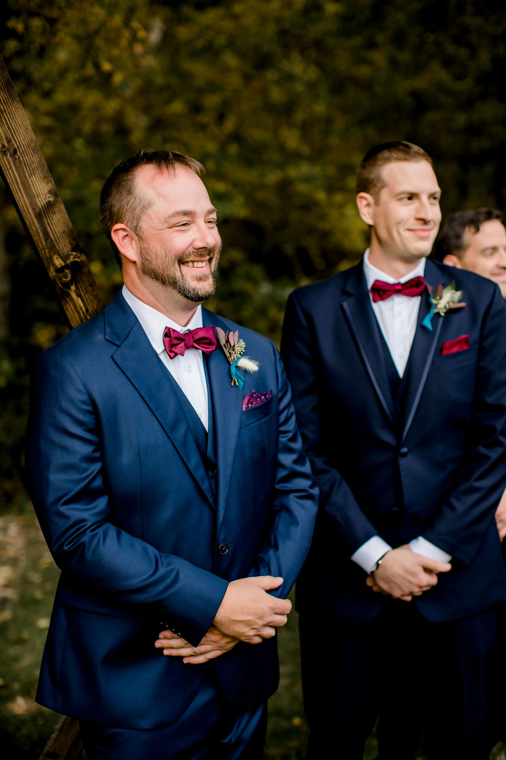 Groom smiling at his bride walking down aisle
