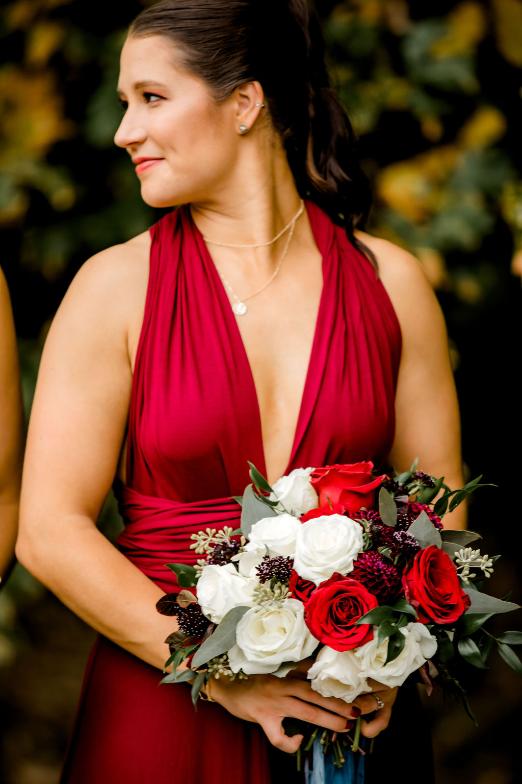 Bridesmaid smiling holding her bouquet