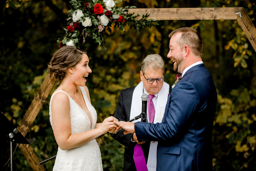 Bride putting ring on grooms hand
