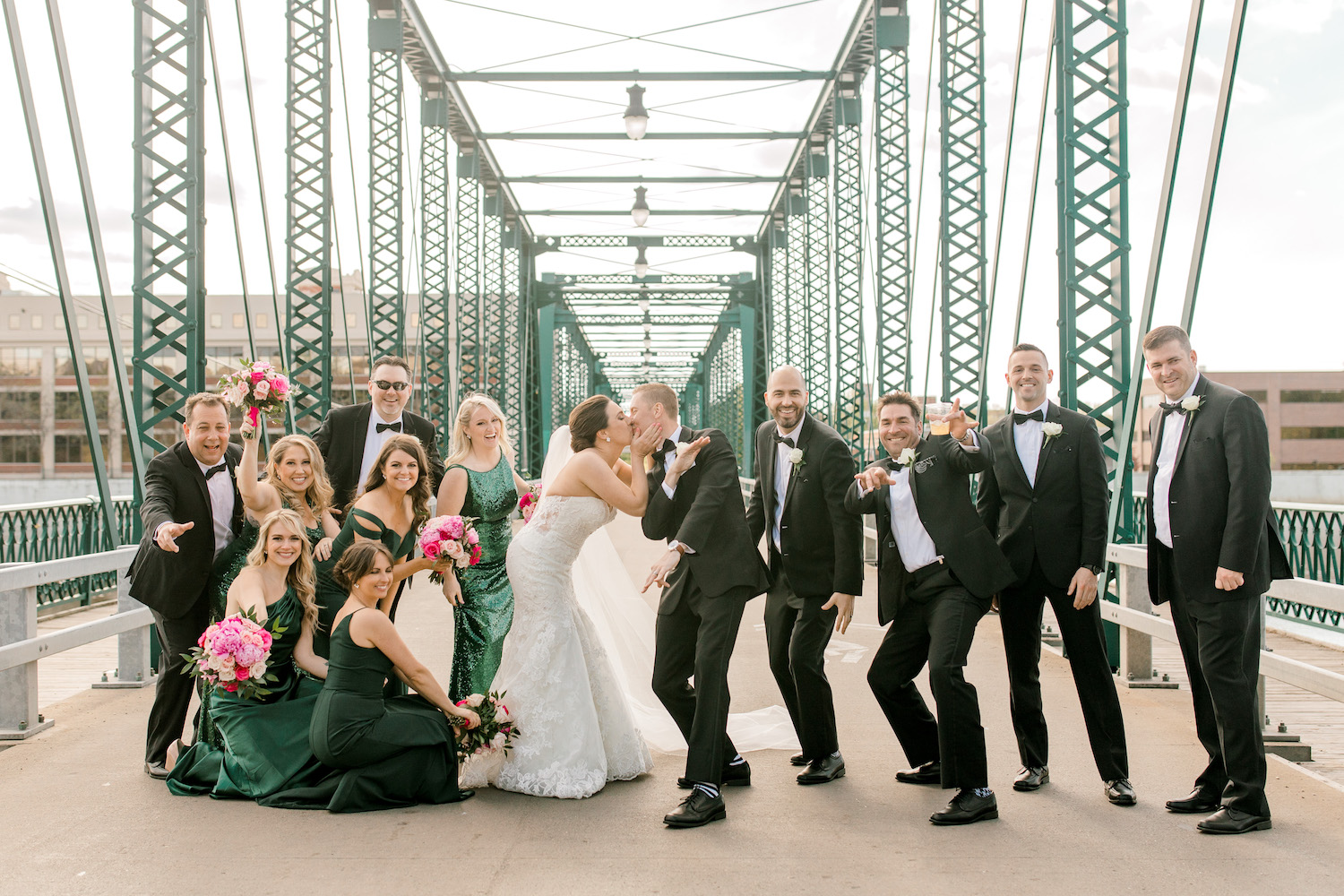 Bridal party celebrating bride and groom kissing