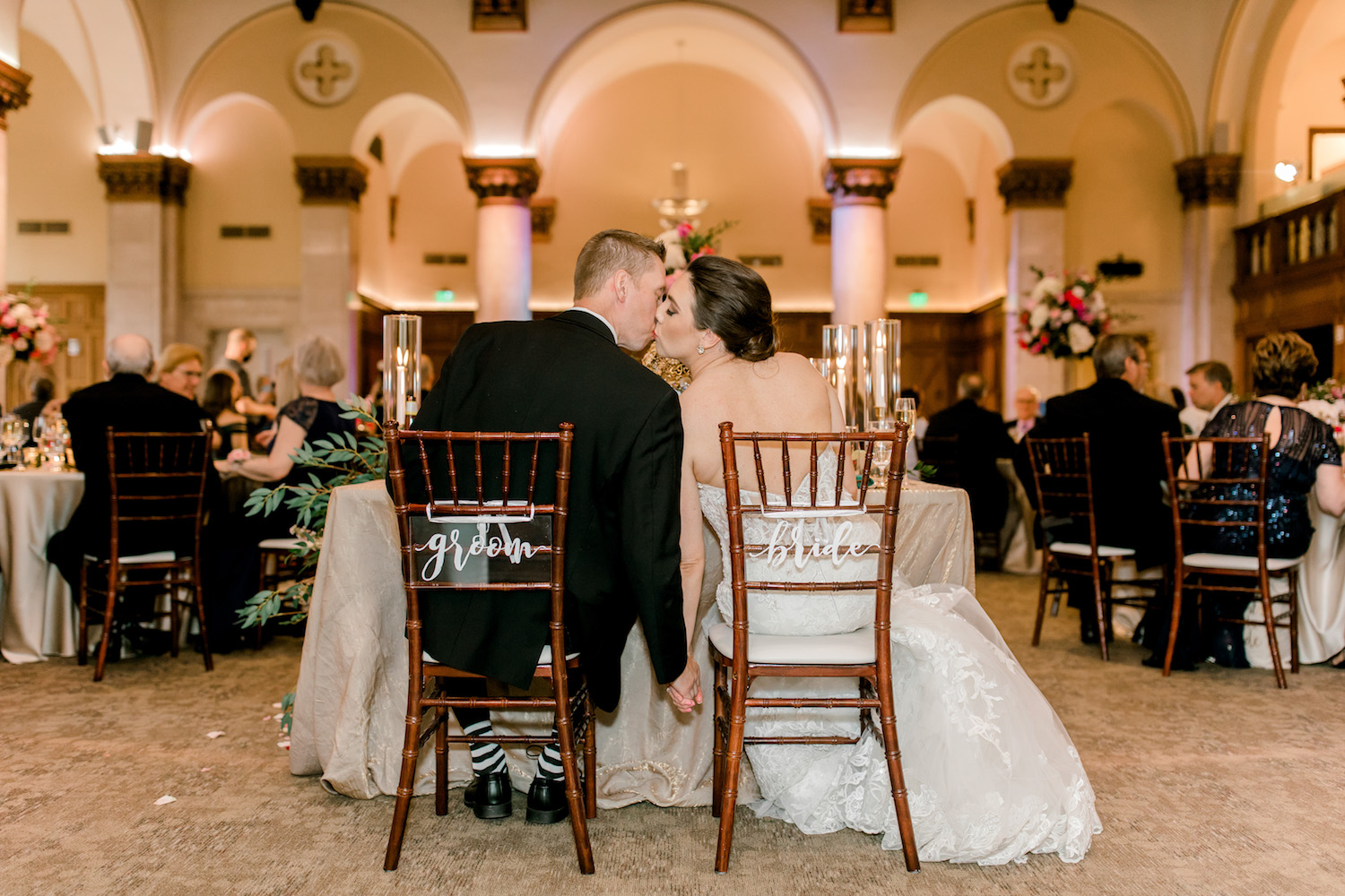 Bride and groom kissing at head table during City Flats Hotel wedding