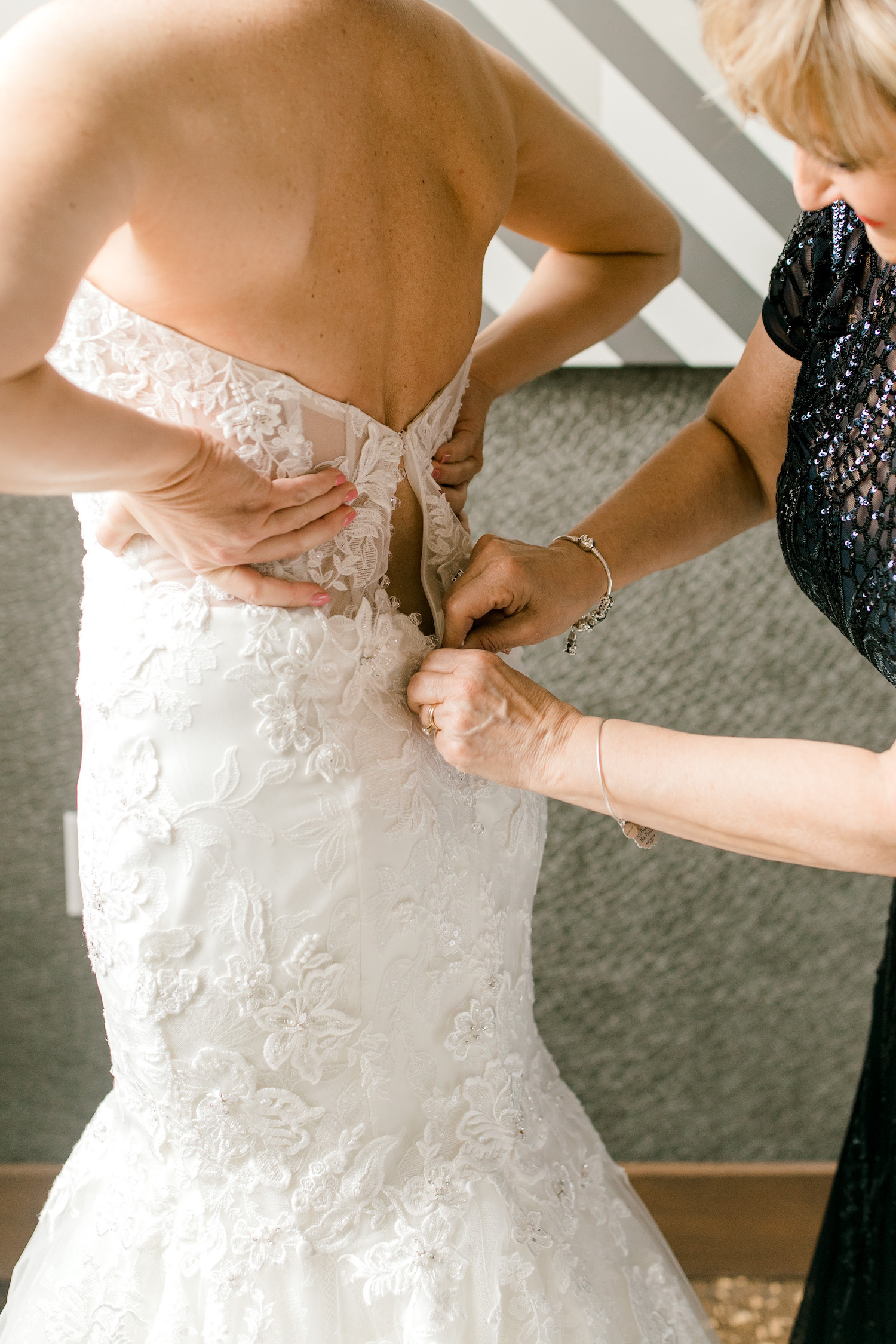 Brides dress being buttoned for her City Flats Hotel wedding